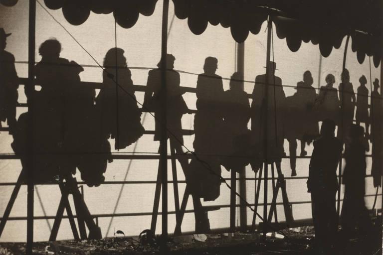 Fotografia em preto e branco mostra silhuetas de público no circo