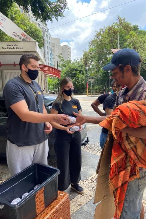 Homem entrega um hambúrguer a morador de rua, que está segurando um cobertor com uma das mãos