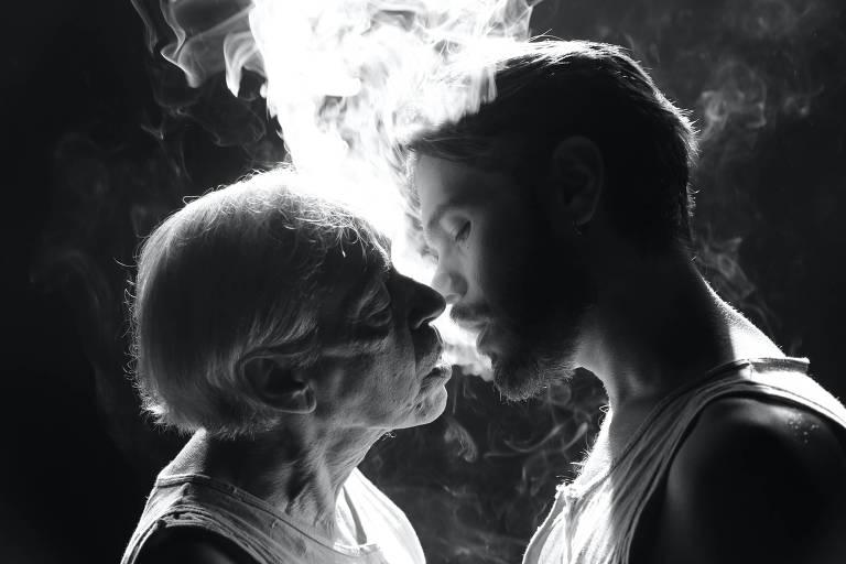 Retrato em preto e branco de dois homens que expiram fumaça na boca um do outro