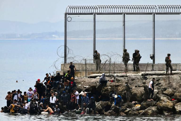 Migrantes sobem em rochas enquanto militares espanhóis patrulham cerca na fronteira do enclave de Ceuta, na África