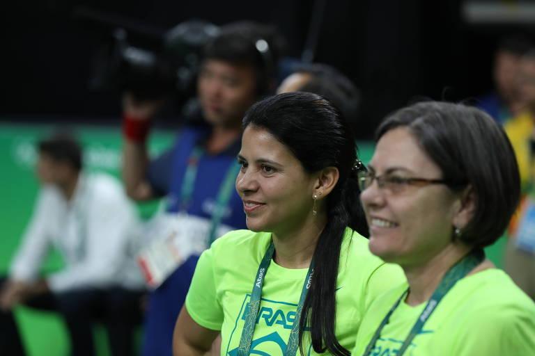 Duas melhores com camisetas verdes da delegação brasileira sorriem em arena olímpica