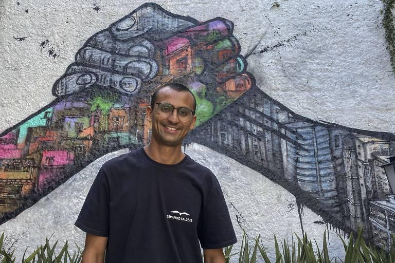 homem de camiseta preta e óculos posa em frente a muro grafitado colorido