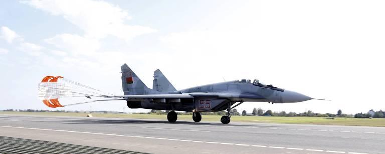 avião militar anda em pista de pouso comum para-quedas aberto em sua cauda