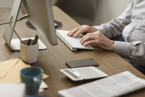Senior retired man sitting ad desk and working with a computer, elderly and technology concept, hands close up