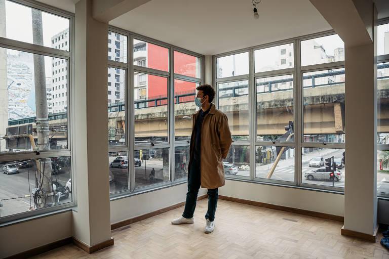 Homem em pé dentro de prédio, ao lado de janela