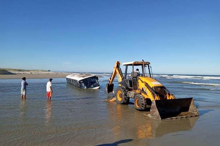 Mar encobre 80% de ônibus encalhado em praia do litoral sul paulista