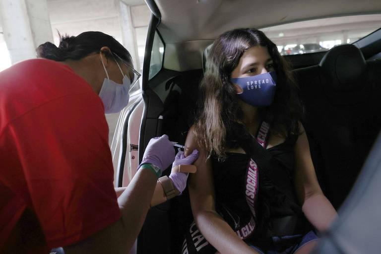Menina com máscara é vacinada no banco de trás de um carro