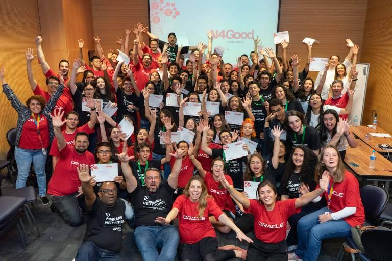 grupo de pessoas segura certificado em mãos e comemora com as mãos para cima. usam camisetas vermelhas e pretas em uma sala com telão ao fundo