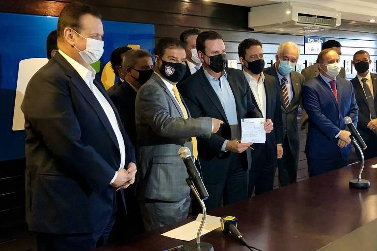 O prefeito do Rio de Janeiro, assina a ficha de filiação ao PSD, em solenidade na sede do partido, em Brasília. À esquerda na foto, o presidente da sigla, Gilberto Kassab, e o senador Nelsinho Trad (PSD-MS)
