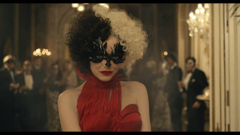 Mulher branca com vestido vermelho e máscara preta em festa
