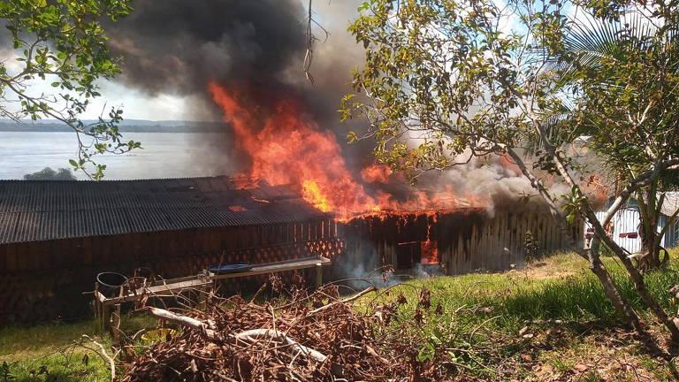 Foto mostra fogo e fumaça em casa, ao redor, árvores