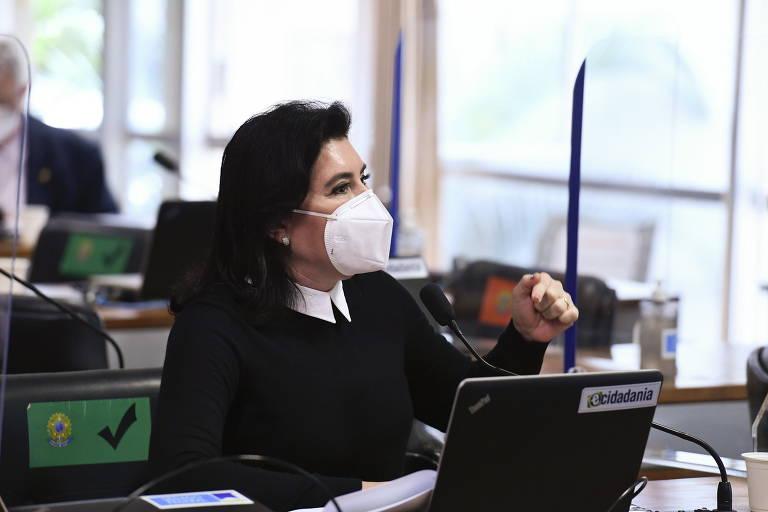 Uma mulher branca, de máscara, gesticulando diante de um notebook que está na bancada