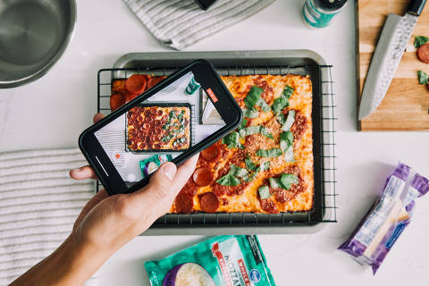 """Newton Nguyen films a cooking video for TikTok at his home in Los Angeles, May 17, 2021. """"A lot of my recipes are from the internet,"""" said Nguyen. """"I'll find something on a friend's Instagram story that looks interesting."""" (Adam Amengual/The New York Times) ORG XMIT: XNYT177"""