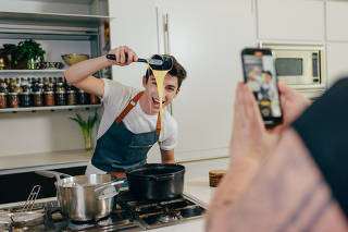Eitan Bernath, a 19-year-old TikTok star with more than 1.6 million followers, films a cooking video at his home in New York, May 17, 2021. (Timothy O'Connell/The New York Times)