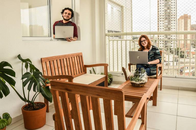 Mulher em varanda segurando computador, sentada, e home em pé, em janela que dá para a varanda, também com computador