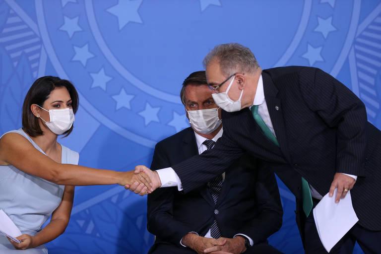 Em frente a painel azul, Michelle Bolsonaro, de vestido azul, cumprimenta Queiroga, de terno escuro, enquanto o presidente observa