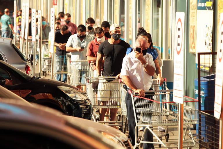Imagem mostra pessoas em fila para entrar em supermercado