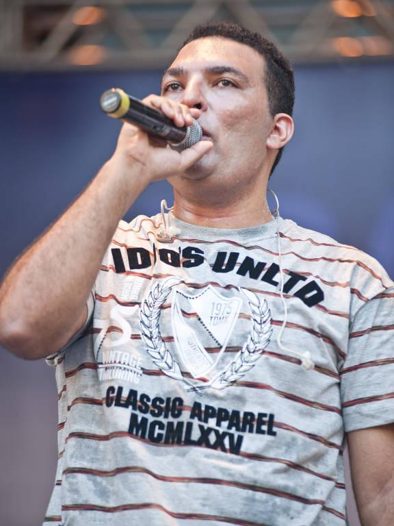 homem de cabelo curto e camiseta listrada segurando um microfone