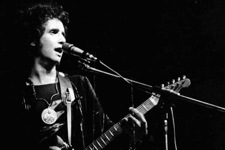 imagem em preto e branco de homem cantando ao microfone e tocando guitarra