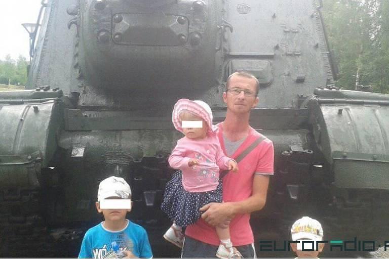 Homem segura uma menina de uns dois anos no colo e duas outras crianças estão ao seu lado, em frente de umcaminhão