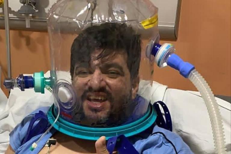 homem com capacete de plástico em cama hospitalar faz sinal positivo com polegar