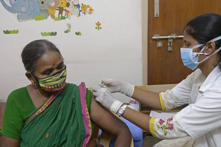 À esquerda, mulher indiana de cabelo preso dividido ao meio e sári verde com detalhes em rosa; ela recebe vacina dada por mulher de branco; ambas estão de máscara