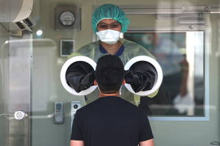 Medical workers use a rapid test for coronavirus disease (COVID-19) on a Taiwanese resident