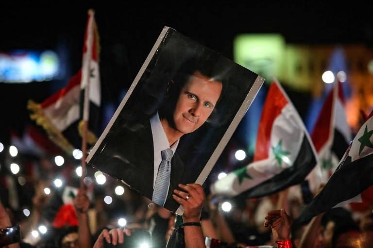 Manifestante exibe cartaz com o rosto de Bashar al-Assad durante celebração em Damasco pela vitória do ditador