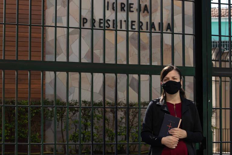 Ela está parada em frente à grade da igreja, de blusa vermelha, casaco e máscara pretos, um livro na mão; ao fundo no muro de pedra se lê IGREJA PRESBITERIANA