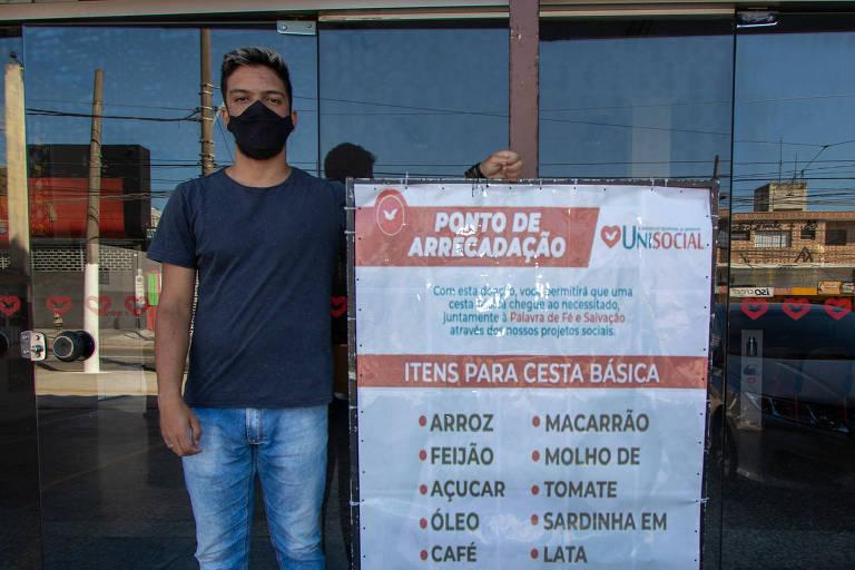Rapaz de camiseta preta e jeans, com máscara preta, em frente a fachada espelhada que reflete a rua e ao lado de cartaz com lista de alimentos para compor cesta básica que podem ser doados à igreja