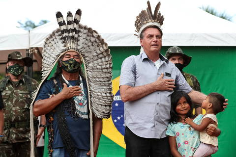 Brazil's President Jair Bolsonaro listens to national anthem next to an indigenous person at the Yanomami tribe reservation bordering Venezuela in Sao Gabriel da Cachoeira, Amazonas state, Brazil, May 27, 2021. Marcos Correa/Handout via REUTERS   ATTENTION EDITORS - THIS IMAGE HAS BEEN SUPPLIED BY A THIRD PARTY. MANDATORY CREDIT ORG XMIT: SMS401