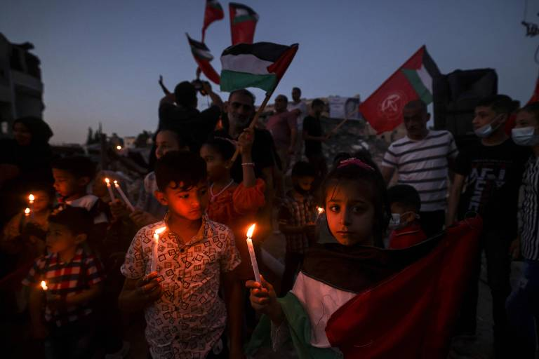 Crianças palestinas vistam um prédio destruído pelos bombardeios israelenses em Beit Lahia, na Faixa de Gaza