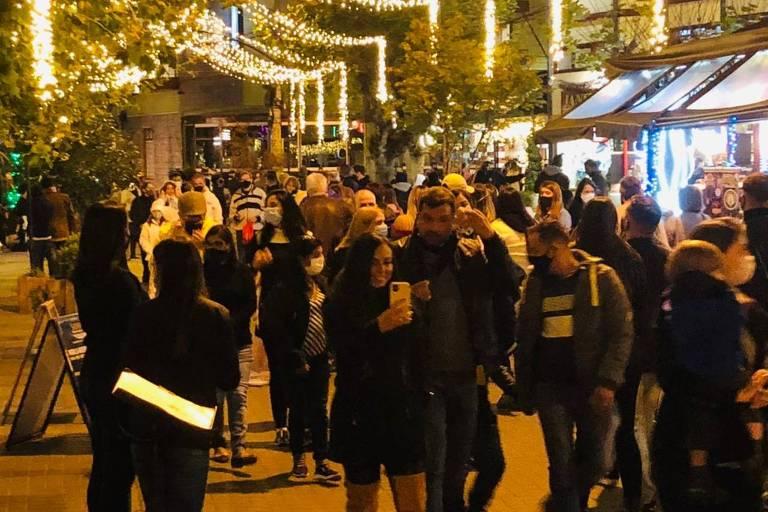 imagens noturnas de rua cheia de pessoas com agasalho de frio e luzes