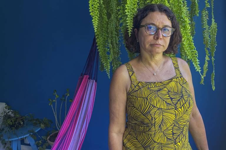 mulher vestida de blusa amarela em frente a parede azul com rede e samambaia ao lado