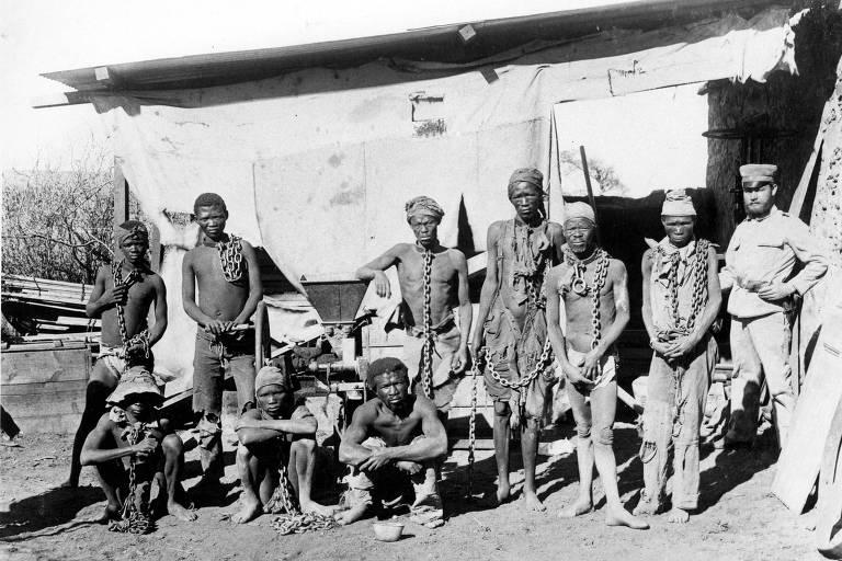 Seis africanos em pé e três agachados ao lado de soldado, em foto em preto e branco