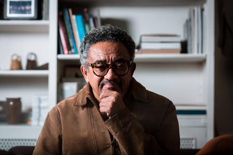 Homem negro de pelo clara, cabelos e cavanhaque grisalhos, óculos de aros grossos, vestido com casaco marrom, com o queixo apoiado na mão esquerda. Ao fundo, uma estante branca com livros e objetos pessoais.