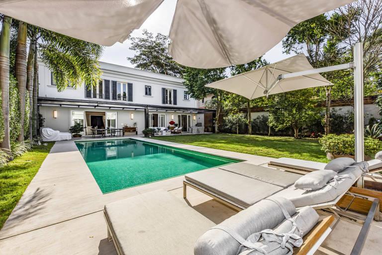 Quintal de casa com piscina e cadeiras