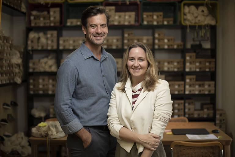 O casal Darren Enthoven e Juliana Lawson, ao lado de caixas de calçados