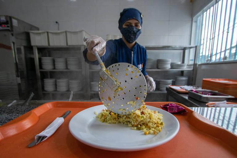 Mulher com touca e máscara serve refeição em prato numa bandeja