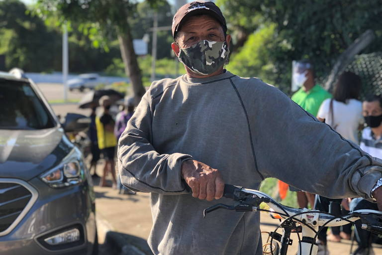 Homem de blusa cinza e máscara de camuflagem se apoia em bicicleta em frente a fila de carros