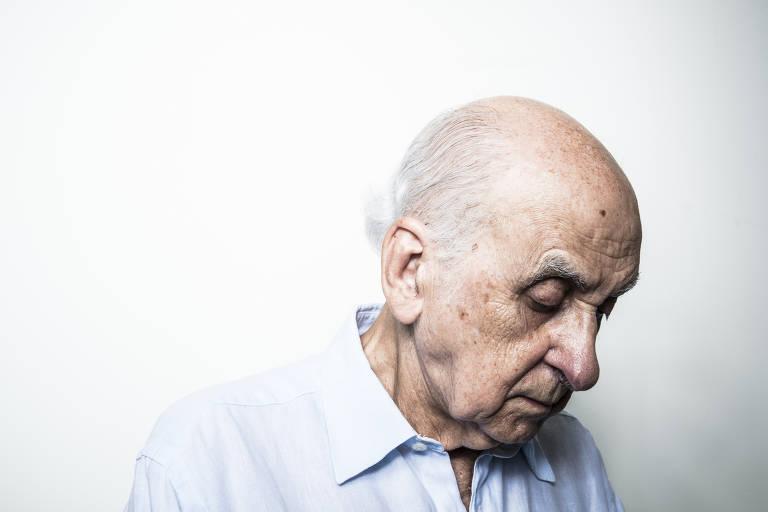 retrato de homem calvo de cabelos brancos de lado com a cabeça levemente inclinada para baixo, ele veste camisa branca mas só vemos até seus ombros