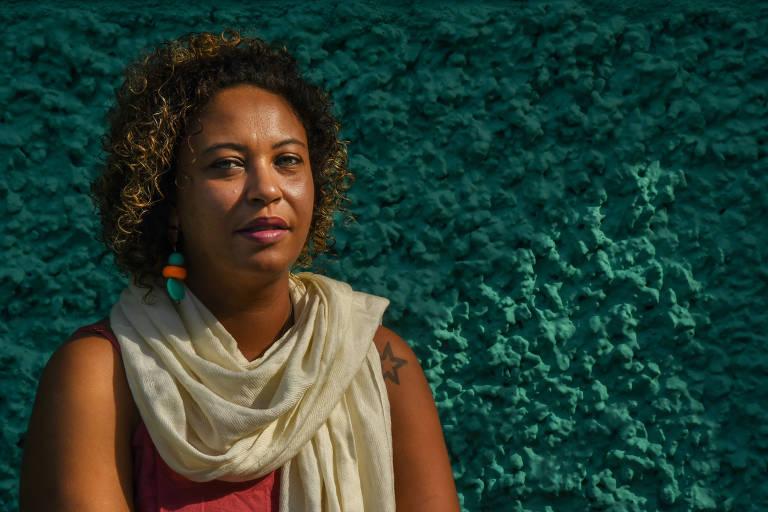 É uma mulher negra, de pele clara, olhos verdes, cabelo na altura do pescoço; está contra uma parede de chapisco verde-água, usa um vestido cor de telha com um xale marfim por cima