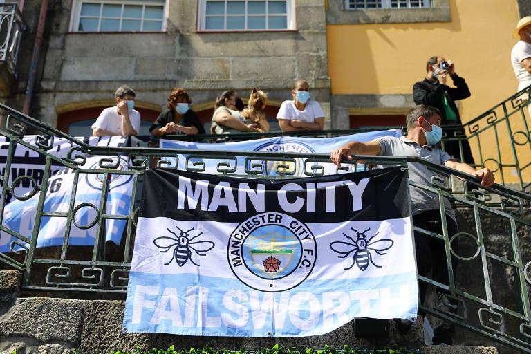 """Pessoas em escada, com faixa escrita """"Man City"""" pendurada"""