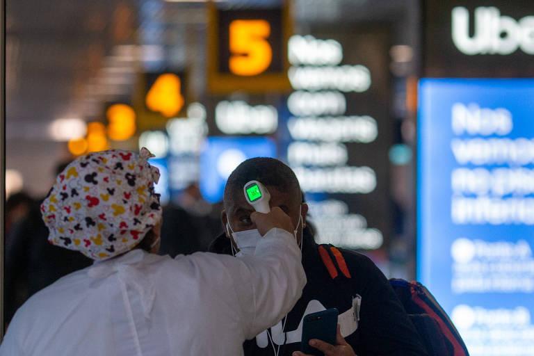 Profissional de saúde mede temperatura de passageiro na barreira sanitária instalada no aeroporto de Congonhas, na zona sul