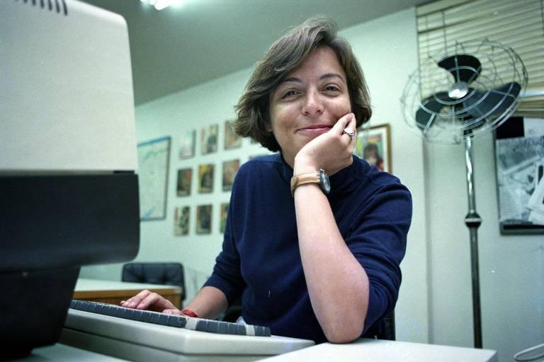 mulher jovem está sentada em uma escrivaninha. ela apoia o rosto em uma das mãos e sorri para a câmera