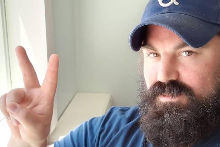 Homem com barba e boné faz sinal de viva com a mãe direita