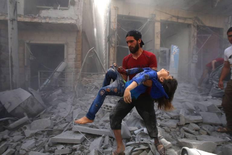 Homem carrega mulher ferida após bombardeio na província de Idlib, na Síria