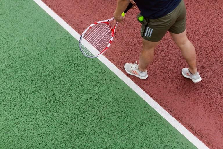 Pernas de homem jogador de tênis, segurando raquete e bolinha no limite da quadra