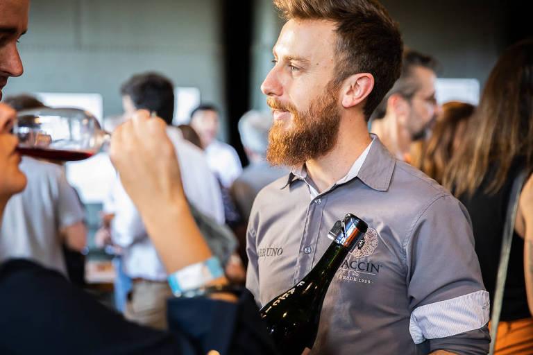 Bruno Faccin segura uma garrafa de vinho e olha para a esquerda da foto. No canto esquerdo uma mulher bebe vinho em uma taça