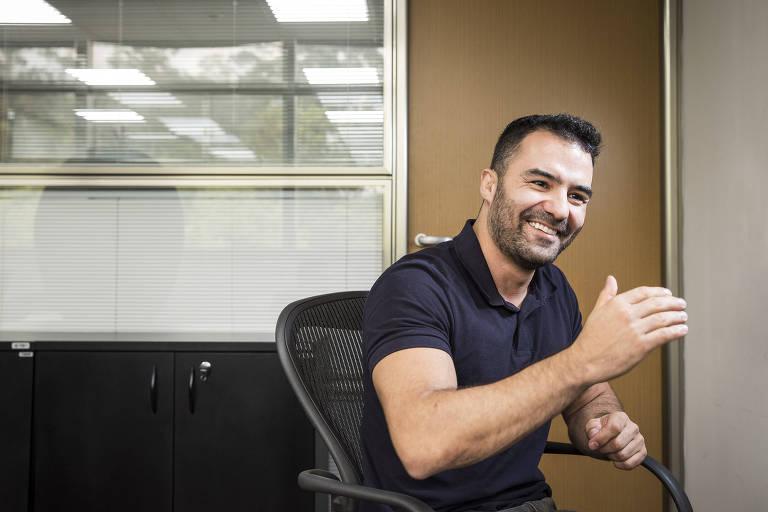 Ele está de camiseta preta, sentado (aparece da barriga para cima), gesticulando com a mão direita